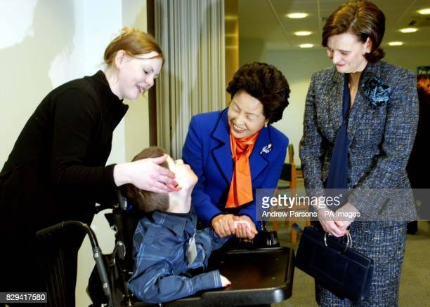 The wife of Britain's Prime Minister Cherie Blair and wife of the President of South Korea Madame Roh talk to Jack Suslak and his enabler Lisa...