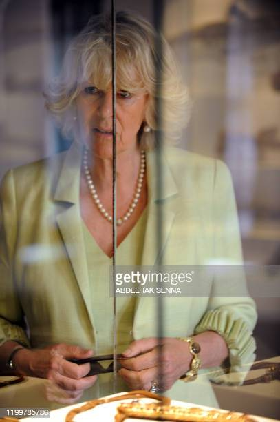 The wife of Britain's Prince Charles Camilla looks out through the glass enclosing an exhibit at the museum in the Oudayas Kasbah a fortified...
