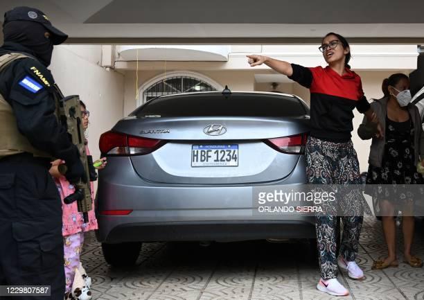 The wife of Jose Alejandro Nunez Cruz, alleged administrator of the criminal gang Mara Salvatrucha 13 , confronts members of the National Anti Maras...
