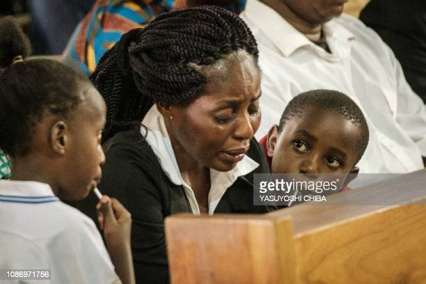 The wife of late Erickson Momanyi a staff member of the Dusit D2 hotel cries between her two children during the memorial service at the Consolata...