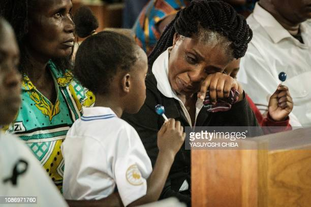 The wife of late Erickson Momanyi, a staff member of the Dusit D2 hotel, cries between her two children during the memorial service at the Consolata...