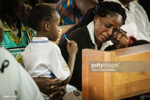 The wife of late Erickson Momanyi, a staff of the DusitD2 hotel, cries beside her two children, during the memorial service on January 23, 2019 for...