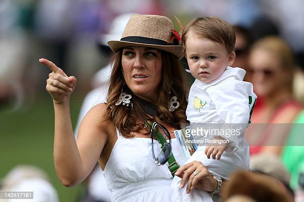 The wife of Rory Sabbatini of South Africa Amy holds their son during the Par 3 Contest prior to the start of the 2012 Masters Tournament at Augusta...