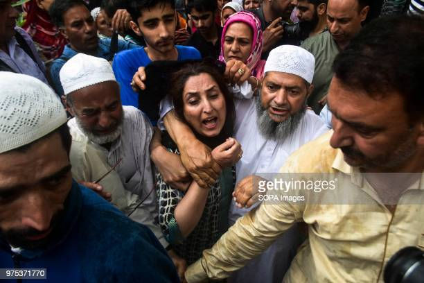 The wife of Shujaat Bukhari veteran journalist and EditorinChief of English daily 'Rising Kashmir' cries during a funeral procession in Kreeri some...