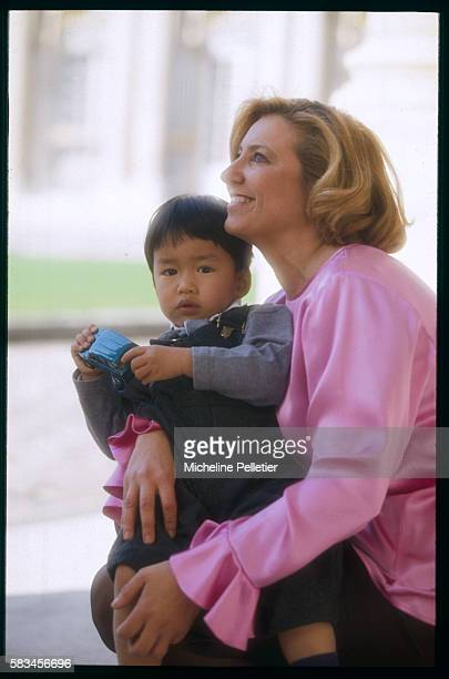 The wife of the French Minister of Culture Dr MarieYvonne DousteBlazy holds their adopted son lovingly