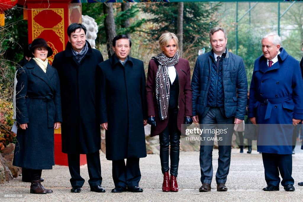 The wife of the French president Brigitte Macron (C), French Junior Minister for Foreign Affairs Jean-Baptiste Lemoyne (2ndR), Chinese vice-foreign minister Zhang Yesui (3rdL) and former French Prime Minister Jean-Pierre Raffarin (R) pose as they arrive to attend a naming ceremony for male panda cub Yuan Meng, which was born at the Beauval zoo, on December 4, 2017 in Saint-Aignan-sur-Cher. The 4-month-old cub was called Yuan Meng, which means 'Fulfillment of a dream'. / AFP PHOTO / POOL / Thibault Camus