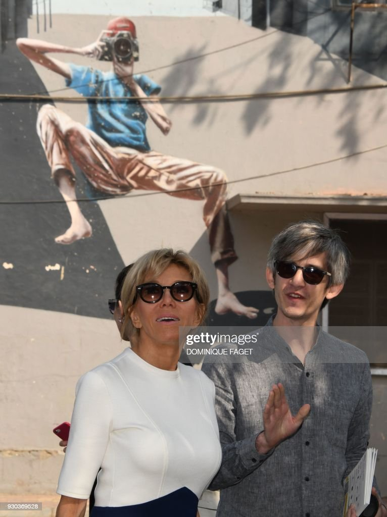The wife of the French President Emmanuel Macron, Brigitte Macron (L), speaks with French architect Pierre Guyot during a visit to Lodhi Colony, known for its street art, in the Indian capital New Delhi on March 11, 2018. Brigitte Macron is visiting India with her husband on an official three-day state visit where they will travel to New Delhi, Agra and Varanasi. /