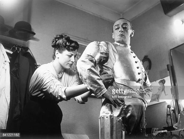 The wife of the Italian comic actor known as Toto helps him into his costume for the show Bada che ti mangio