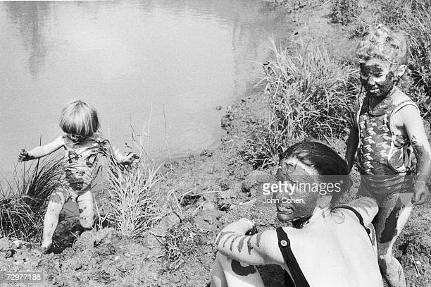 The wife Penny and two children Rufus and Sonya of the photographer appear partially covered in mud as they enjoy themselves by a pond or similar...