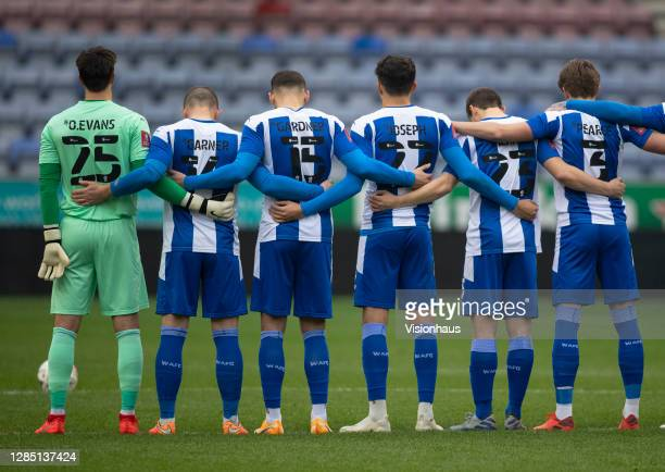 The Wigan Athletic team line up to respect a minutes silence for Remembrance Sunday before the FA Cup 1st round match between Wigan Athletic and...