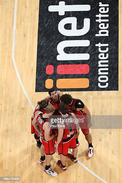 The Wildcats form a huddle on the court as Kevin Lisch looks to the scoreboard during game two of the NBL Grand Final series between the Perth...