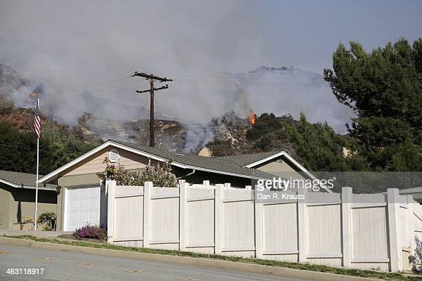 The wildfires burn in foothiills behind properties on January 16 2014 in Azusa California Authorities have stated that three people have been charged...