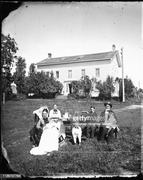 The William McFarland family is gathered around a table covered with books pine cones glassware and flowers in front of their Exchange Street house...