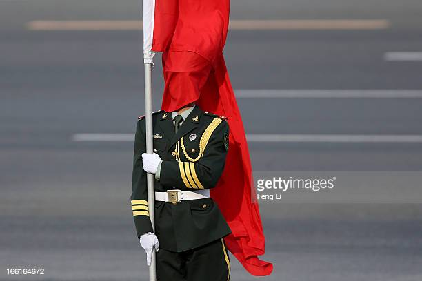 The wind blows a red flag onto the face of an honour guard before a welcome ceremony for Australia's Prime Minister Julia Gillard outside the Great...