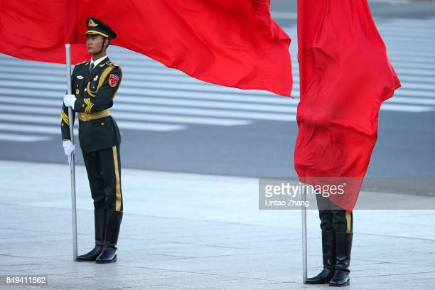 The wind blows a red flag onto the face of an honour guard during a welcoming ceremony for Singapore Prime Minister Lee Hsien Loong outside the Great...