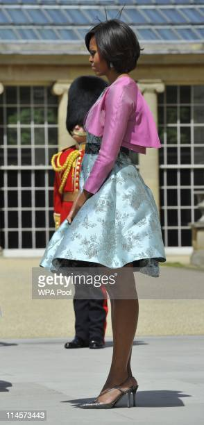 The wind blows First Lady Michelle Obama's skirt as she stands during a ceremonial welcome in the garden of Buckingham Palace on May 24 2011 in...