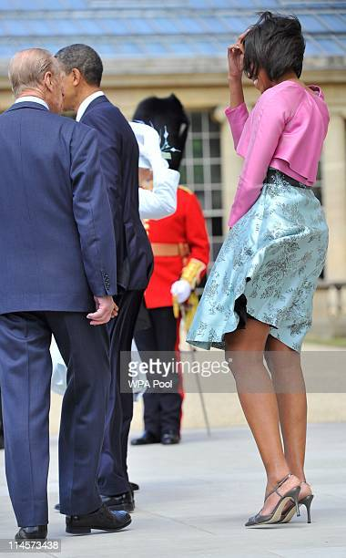 The wind blows First Lady Michelle Obama's skirt as she stands with US President Barack Obama and Prince Philip Duke of Edinburgh during a ceremonial...