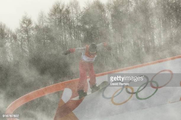 The wind blows snow across the course as a competitor practices before the Snowboard Ladies's Slopestyle Qualification was cancelled due to weather...