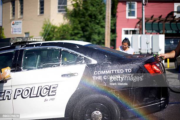 The Windber High School softball team rinses a police car as part of their car wash fundraiser on August 13 2016 in Windber Pennsylvania The small...