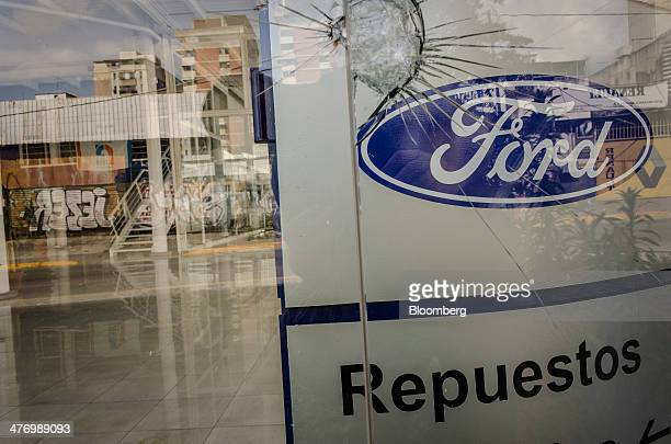 The window of a closed Ford Motor Co dealership is cracked in the Altamira section of Caracas Venezuela on Friday Feb 28 2014 Antigovernment protests...
