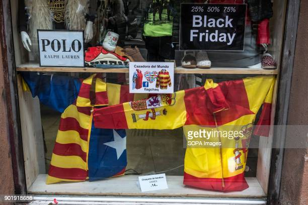 The window of a store shows simultaneously different models of clothes for supporters of Spain and also for freedom catalonia fightersSince 2...