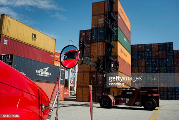 The windshield of a truck reflects in a side mirror as a top loader prepares to move a shipping container at the Port of Savannah in Savannah,...