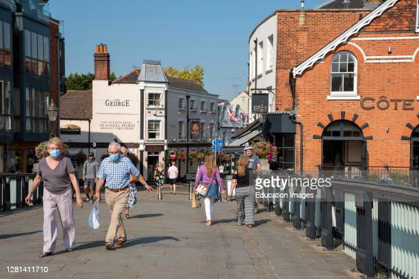 The Windsor and Eton bridge located between two towns with tourists and shoppers some wearing masks cross the bridge during Covid outbreak, Eton,...