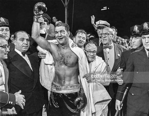 The winner and new World Heavyweight Champion Rocky Marciano by virtue of a 13th round knockout poses for a portrait Looking over Marciano's shoulder...