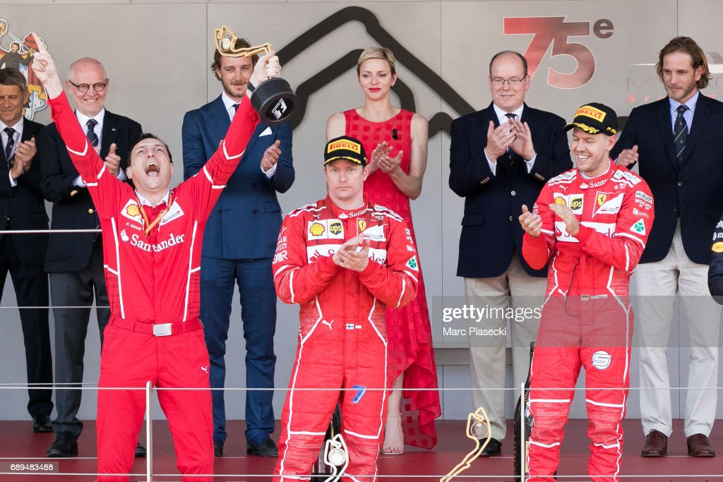 The winner German driver Sebastian Vettel (R) celebrates on the podium next to second place driver Finn Kimi Raikkonen (C) after the Monaco Formula 1 Grand Prix at the Monaco street circuit, on May 28, 2017 in Monaco.