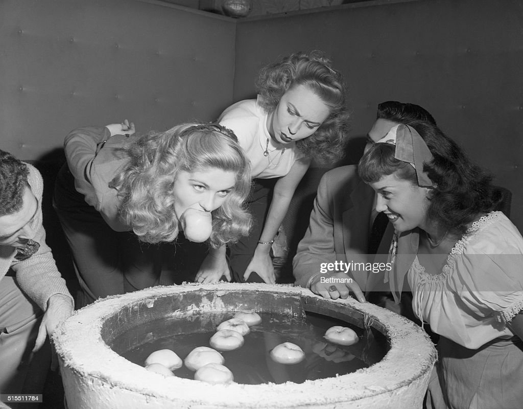 Teenagers Bobbing for Apples : News Photo