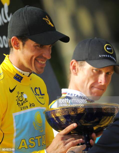 The winner of 2009 Tour de France cycling race Kazakh cycling team Astana 's leader Alberto Contador of Spain takes his trophy on the podium as his...