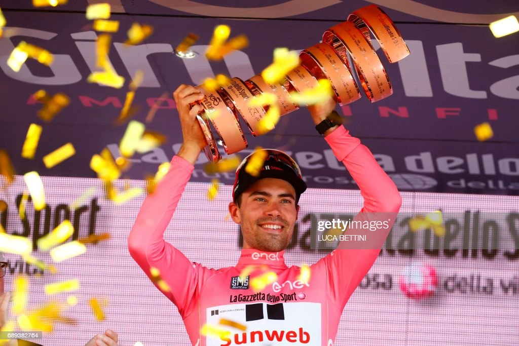 TOPSHOT - The winner of the 100th Giro d'Italia, Tour of Italy cycling race, Netherlands' Tom Dumoulin of team Sunweb holds the trophy on the podium after the last stage, an individual time-trial between Monza and Milan, on May 28, 2017. Tom Dumoulin won the Giro 100 ahead of Colombia's Nairo Quintana of team Movistar, second, and Italy's rider of team Bahrain - Merida, Vincenzo Nibali, third. / AFP PHOTO / Luca Bettini