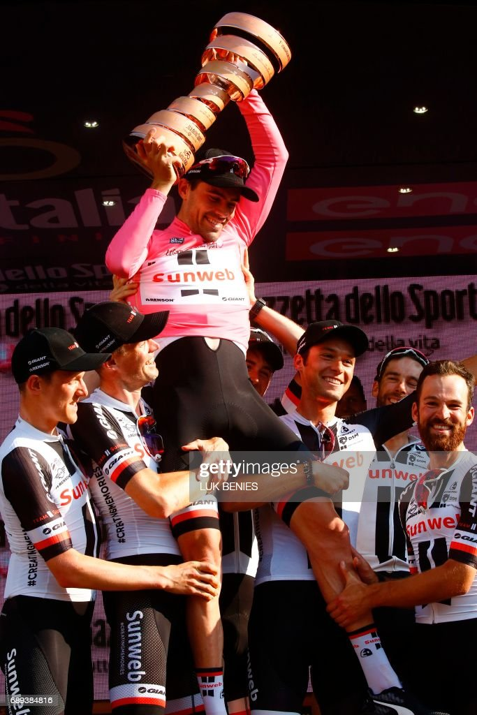 The winner of the 100th Giro d'Italia, Tour of Italy cycling race, Netherlands' Tom Dumoulin (top) of team Sunweb celebrates with teammates on the podium after the last stage, an individual time-trial between Monza and Milan, on May 28, 2017. Tom Dumoulin won the Giro 100 ahead of Colombia's Nairo Quintana of team Movistar, second, and Italy's rider of team Bahrain - Merida, Vincenzo Nibali, third. / AFP PHOTO / Luk BENIES