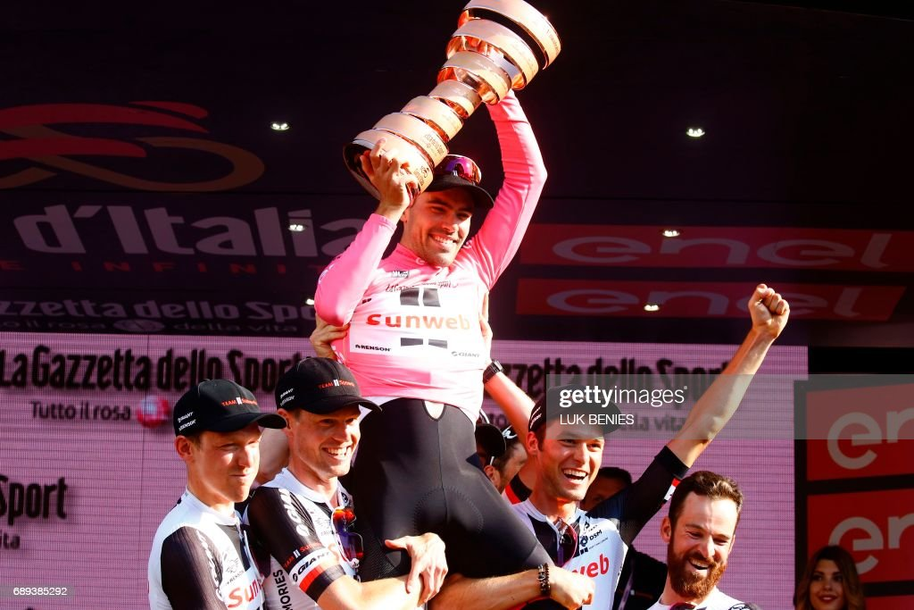 TOPSHOT - The winner of the 100th Giro d'Italia, Tour of Italy cycling race, Netherlands' Tom Dumoulin (top) of team Sunweb celebrates with teammates on the podium after the last stage, an individual time-trial between Monza and Milan, on May 28, 2017. Tom Dumoulin won the Giro 100 ahead of Colombia's Nairo Quintana of team Movistar, second, and Italy's rider of team Bahrain - Merida, Vincenzo Nibali, third. / AFP PHOTO / Luk BENIES