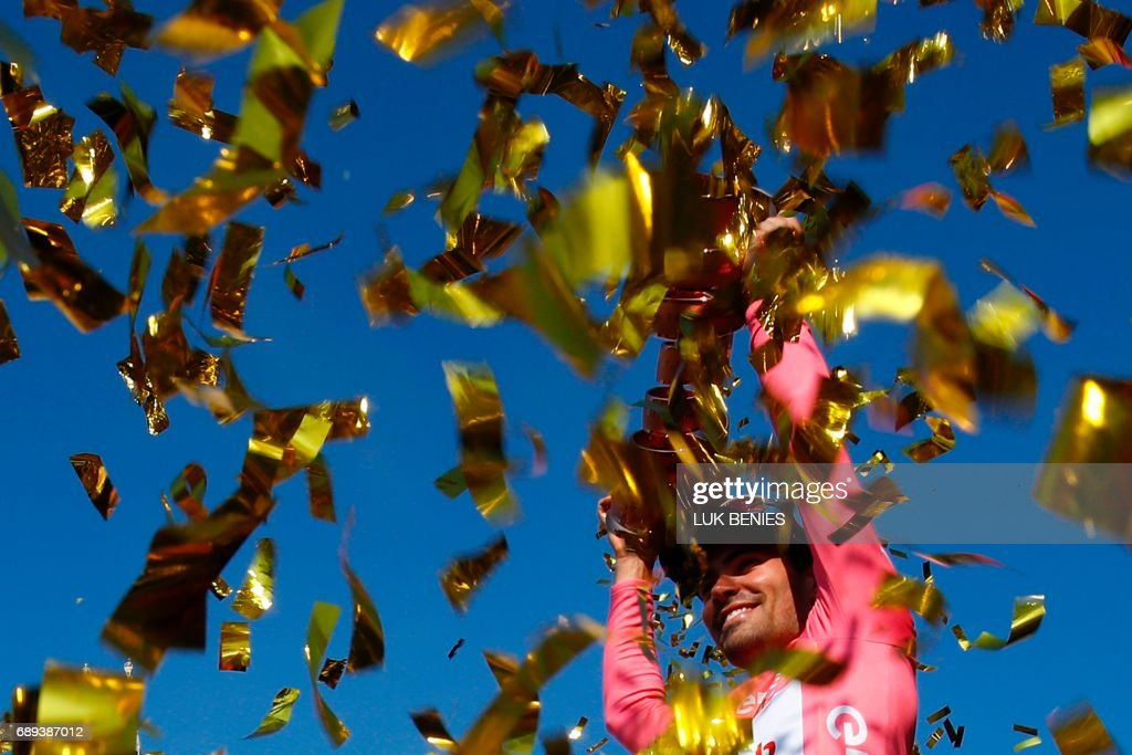 The winner of the 100th Giro d'Italia, Tour of Italy cycling race, Netherlands' Tom Dumoulin of team Sunweb holds the trophy on the podium near Milan's cathedral after the last stage, an individual time-trial between Monza and Milan, on May 28, 2017. Tom Dumoulin won the Giro 100 ahead of Colombia's Nairo Quintana of team Movistar, second, and Italy's rider of team Bahrain - Merida, Vincenzo Nibali, third. / AFP PHOTO / Luk BENIES