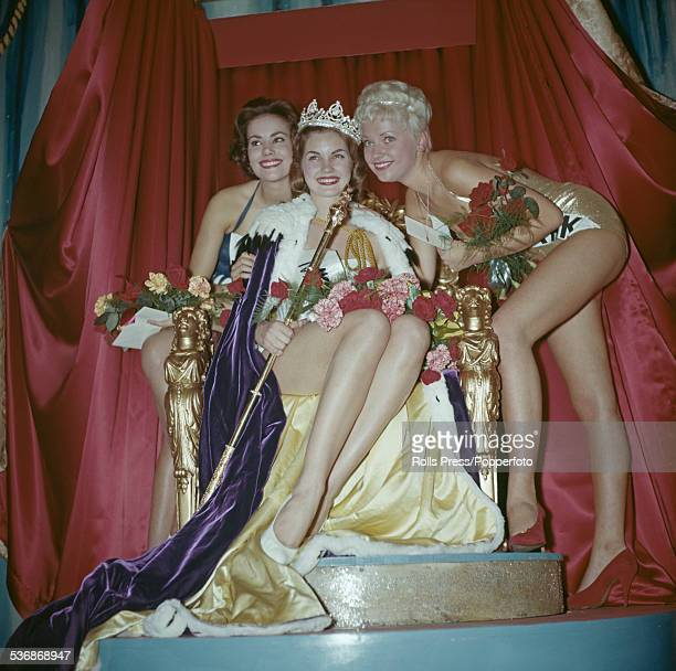 The winner of the 1958 Miss World beauty contest Penelope Coelen of South Africa is pictured sitting on a throne and wearing a crown flanked by on...