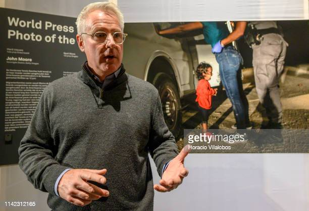 The winner of the 2019 World Press Photo of the Year award Getty Images photographer John Moore stands before the picture while briefing visitors on...