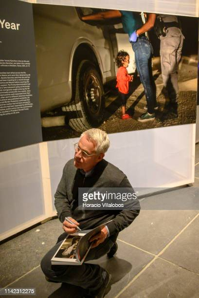 The winner of the 2019 World Press Photo of the Year award Getty Images photographer John Moore signs the page of 2019 WPP catalog with his photo at...