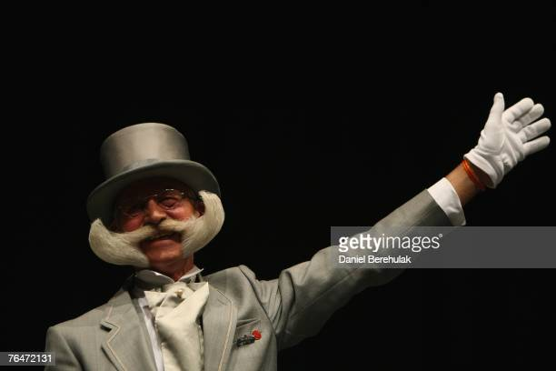 The winner of the Imperial Partial Beard category celebrates victory during the World Beard and Moustache Championships at the Brighton Centre on...