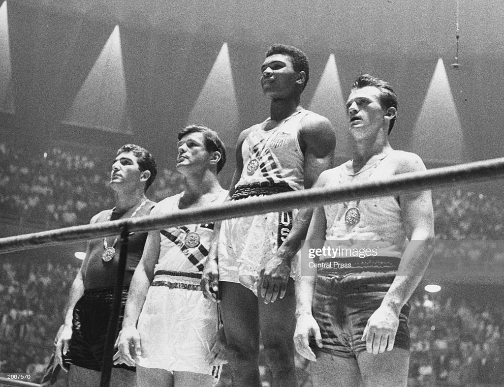 The winners of the 1960 Olympic medals for light heavyweight boxing on the winners' podium at Rome: Cassius Clay (now Muhammad Ali) (C), gold; Zbigniew Pietrzykowski of Poland (R), silver; and Giulio Saraudi (Italy) and Anthony Madigan (Australia), joint bronze.
