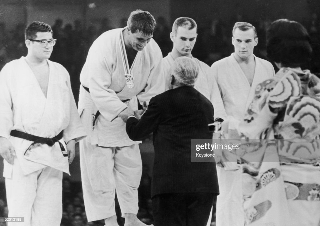 The winners of the Judo Men's Openweight event line up for their medals at the Tokyo Olympics, 24th October 1964. From left to right, they are Akio Kaminaga of Japan (silver), Anton Geesink of the Netherlands (gold) and Theodore Boronovskis and Klaus Glahn