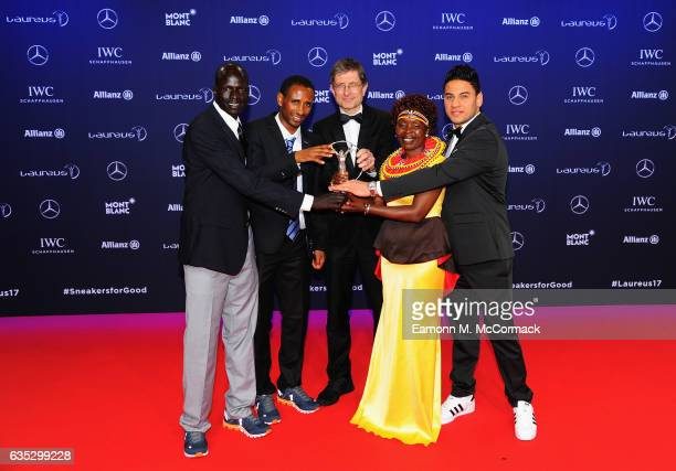 The Winners of the Laureus Sport for Good the Olympic Refugee team pose with their trophy and Laureus Academy Member Tegla Loroupe at the Winners...
