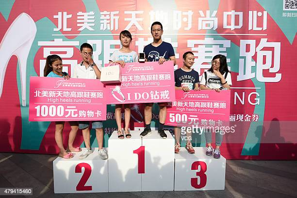 The winners pose with prizes on a podium after a highheel race in front of a shopping mall on July 3 2015 in Taiyuan China The winner got a diamond...