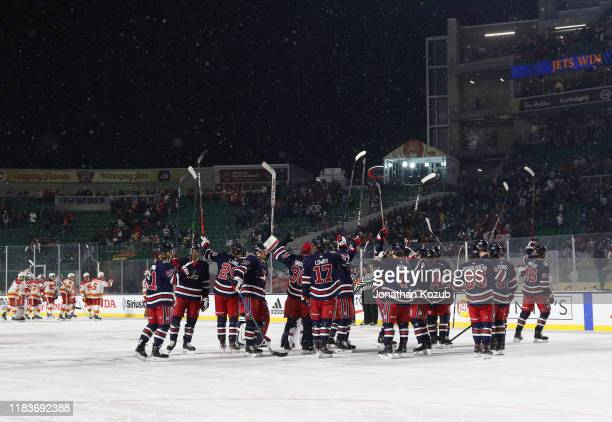 The Winnipeg Jets celebrate their 2-1 overtime win against the Calgary Flames in the 2019 Tim Hortons NHL Heritage Classic between the Calgary Flames...
