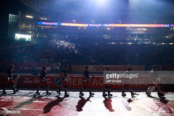 The Winnipeg Jets make their way to the ice prior to the 2019 Tim Hortons NHL Heritage Classic between the Calgary Flames and the Winnipeg Jets at...