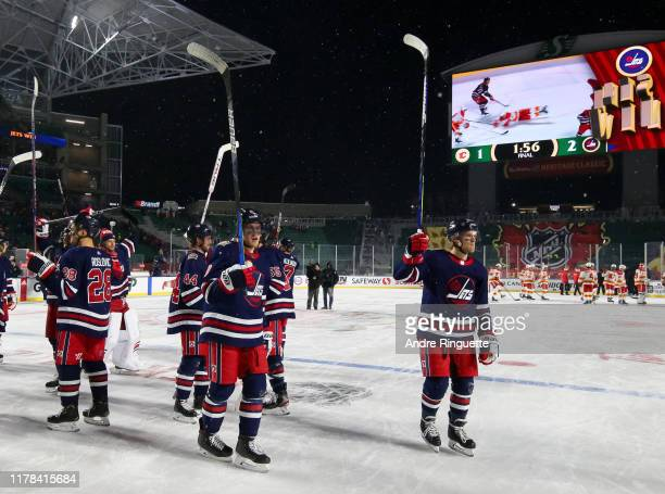 The Winnipeg Jets salute the crowd after defeating the Calgary Flames 2-1 in overtime during the 2019 Tim Hortons NHL Heritage Classic at Mosaic...