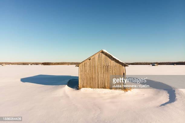 the winter sun creates strong shadows on the snowy fields. the barn house stands alone on the fields - heinovirta stock pictures, royalty-free photos & images