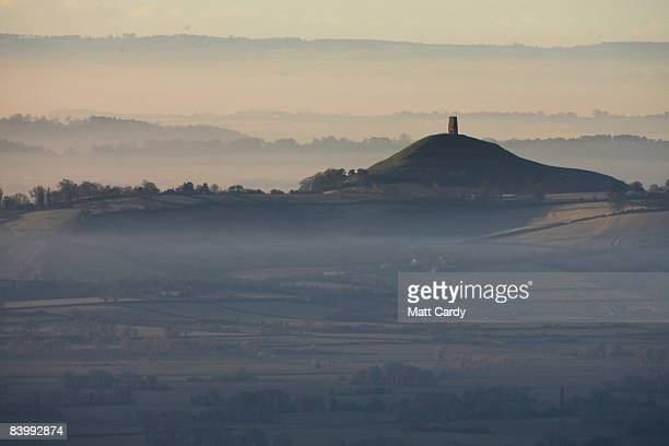 The winter sun rises over mist and frost surrounding the Glastonbury Tor viewed from the Mendip Hills on December 11 2008 in Somerset England Named...