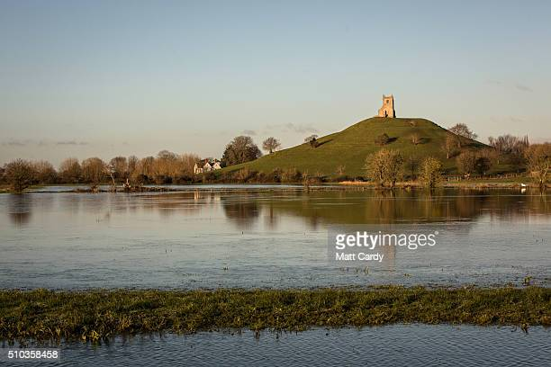 The winter suns rises over flood water still lingering in fields on the Somerset Levels below Burrow Mump and the ruins of St Michael's church on...