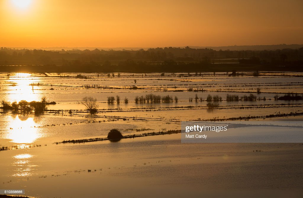 The winter suns rises over flood water still lingering in fields on the Somerset Levels below Burrow Mump on February 15, 2016 in Burrowbridge, England. Following Storm Imogen last week, many parts of the UK are now experiencing the coldest temperatures of the year so far, with overnight temperatures as low as -14C recorded in rural Scotland. However, despite the Met Office issuing a severe weather warnings for snow and ice, more wet and windy weather is forecasted later this week with bookmakers slashing the odds that this February is set to be the wettest on record.